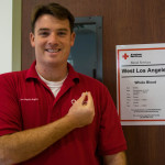 Joe Edwards holds his 5-gallon blood donor pin.